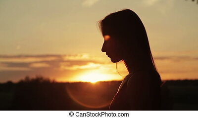 Young woman praying in the forest at sunset - Silhouette of...