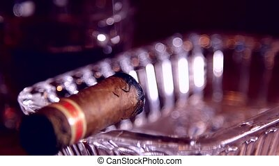 Cigar is in the crystal ashtray - Cuban cigar smoldering in...