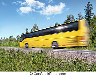 yellow tourist bus speeding on rural highway, motion blur, with reflecting sun