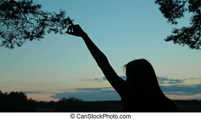 Young woman dancing in the forest after sunset. Freedom and...