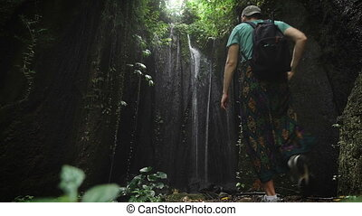 Young man in a cap and a backpack has reached an incredibly beautiful waterfall in the jungle. Tourist enjoying the unspoilt beauty of nature.