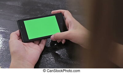 Woman using smartphone with green screen. Close up shot of...