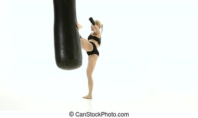 Woman kickboxer with passion warming up with a punching bag,...