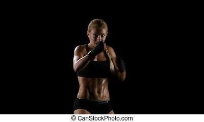 Muscular body of a woman boxer during a training, punches...