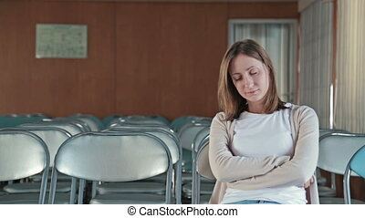 Woman falls asleep in the empty conference hall of cruise...