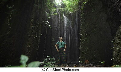 Stylish male explorer resting on a rock in cave near a waterfall behind him. Young man standing in bay inside the mountain. Traveler relaxing inside of tropical botanical garden with cooling cascade.