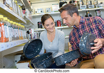 Couple looking at enamel cooking dishes