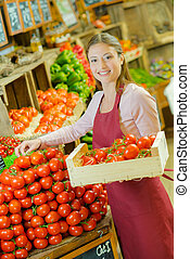 Shop assistant piling up tomatoes