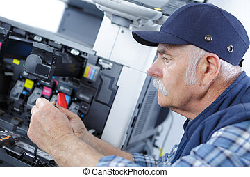 male senior technician is repairing a printer at office