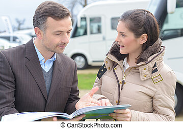 Woman looking at brochure with vehicle salesman