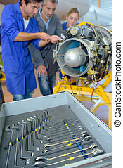 Engineers working on aircraft component