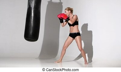 Boxer girl makes blows a punching bag with all passion -...