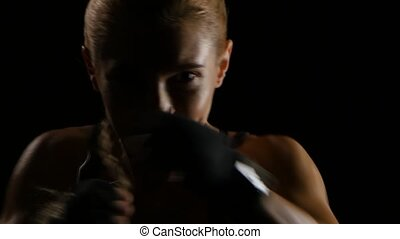 Silhouette of a beautiful woman boxer throwing punches. Close shot