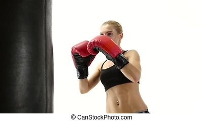 Close shot of a girl kickboxer which kicking punching bag,...