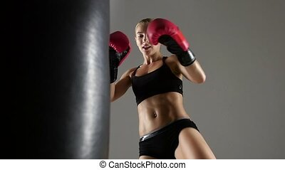Kicking on the punching bag by a woman boxer, dressed in...