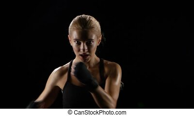 Girl makes blows by hands looking at the camera, training...