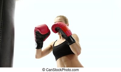 Close shot of female boxer makes blows to punching bag,...