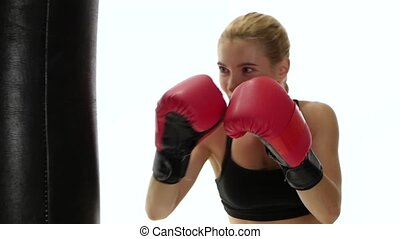 Muscular blond girl boxer with cries kicking punching bag -...