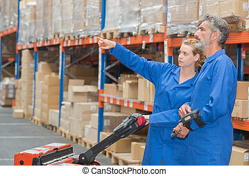 Two warehouse workers with pallet truck, pointing
