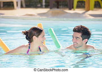 Man and woman in swimming pool with floats