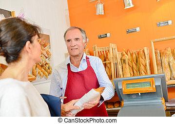 baker serving baguette