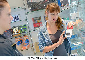 Saleswoman holding memory device with customer