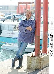 man waiting at seaport