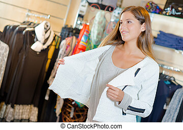 Lady trying on jacket in clothes shop