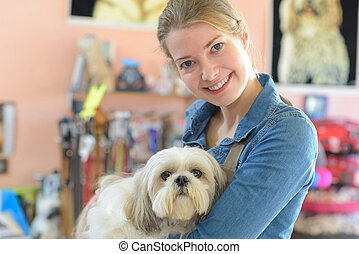 portrait of young woman and her dog in pet store