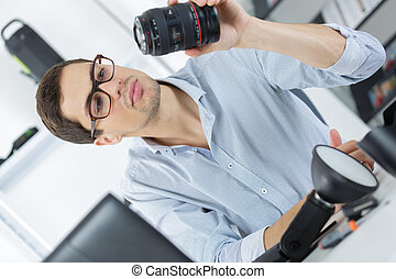 man looking at broken photographic lense