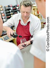 Wine merchant pouring some wine
