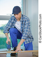 builder worker in safety protective equipment assembling construction frame
