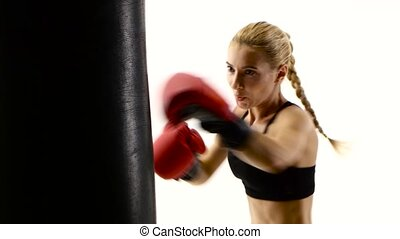 Girl boxer with passion beats his fist on punching bag -...