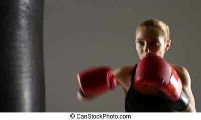 Beautiful girl boxer working with a punching bag. Gray...