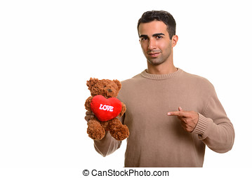 Young handsome Caucasian man holding teddy bear with heart...