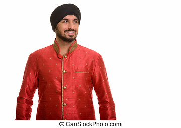 Young happy Indian Sikh thinking while wearing traditional...