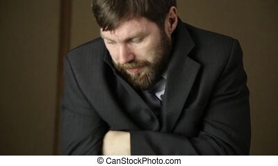 bearded business executive man wears a jacket, yawning and shaking from a cold on a next day after a party. hides ring in his pocket