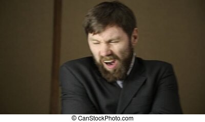 bearded business executive man wears a jacket, yawning and shaking from a cold on a next day after a party