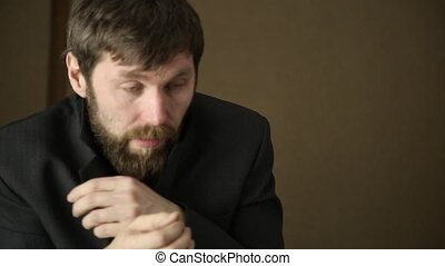 bearded business executive man wears a jacket, yawning and...
