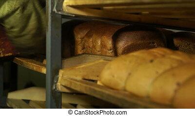 Shaped bread in a workshop. - Baked bread on a wooden shelf...