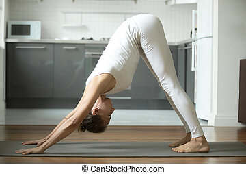 Woman standing in Downward facing dog exercise - Sporty...
