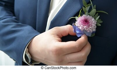 Groom in jacket corrects boutonniere before wedding
