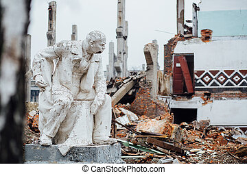 Damaged Lenin statue sitting on a chair with  book in his hand.