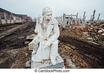 Damaged Lenin statue sitting on a chair with book in his...