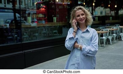 Blonde girl speaks on the phone near a shopping window