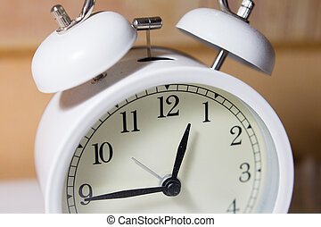 White retro alarm clock with fifteen minutes to one o'clock.