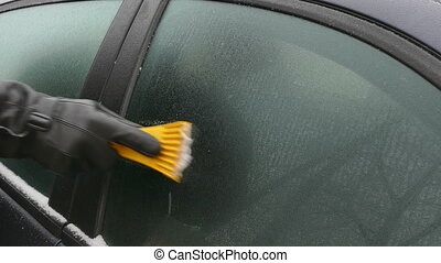 Driver scraping ice from windshield - Winter scene, human...
