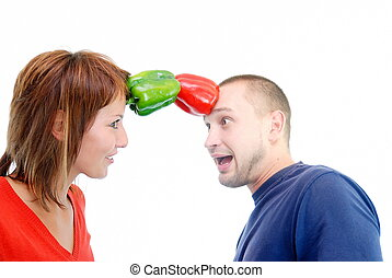 happy couple holding peppers with head - romance with...