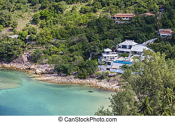 Tropical bungalow on a rocky beach next to the sea. Koh...