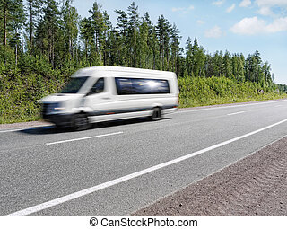 white mini bus speeding on country highway, motion blur -...